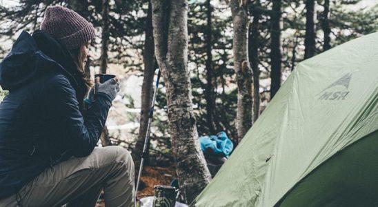 une femme à côté de sa tente